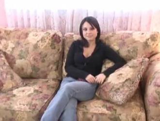 عارضة أزياء سمراء شرائط ويقف على السرير.